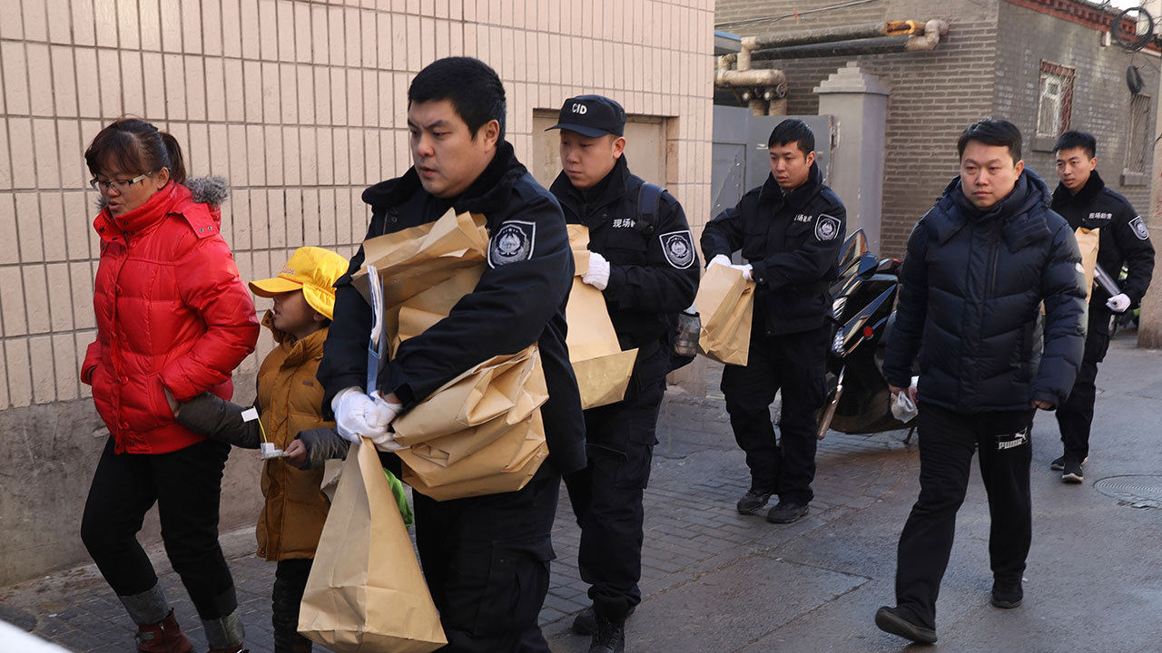 A woman walks with a child as they leave from the Beijing No. 1 Affiliated Elementary School of Xuanwu Normal School near crime scene investigators in Beijing on Jan. 8, 2019.