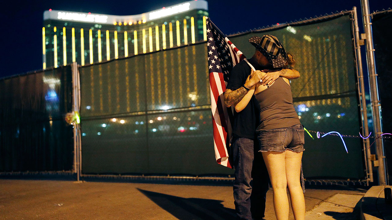 Kenneth Wright, left, embraces Cara Knoedler on the anniversary of the Oct. 1, 2017 mass shooting, Monday, Oct. 1, 2018, in Las Vegas. Behind them is the site of the shooting.