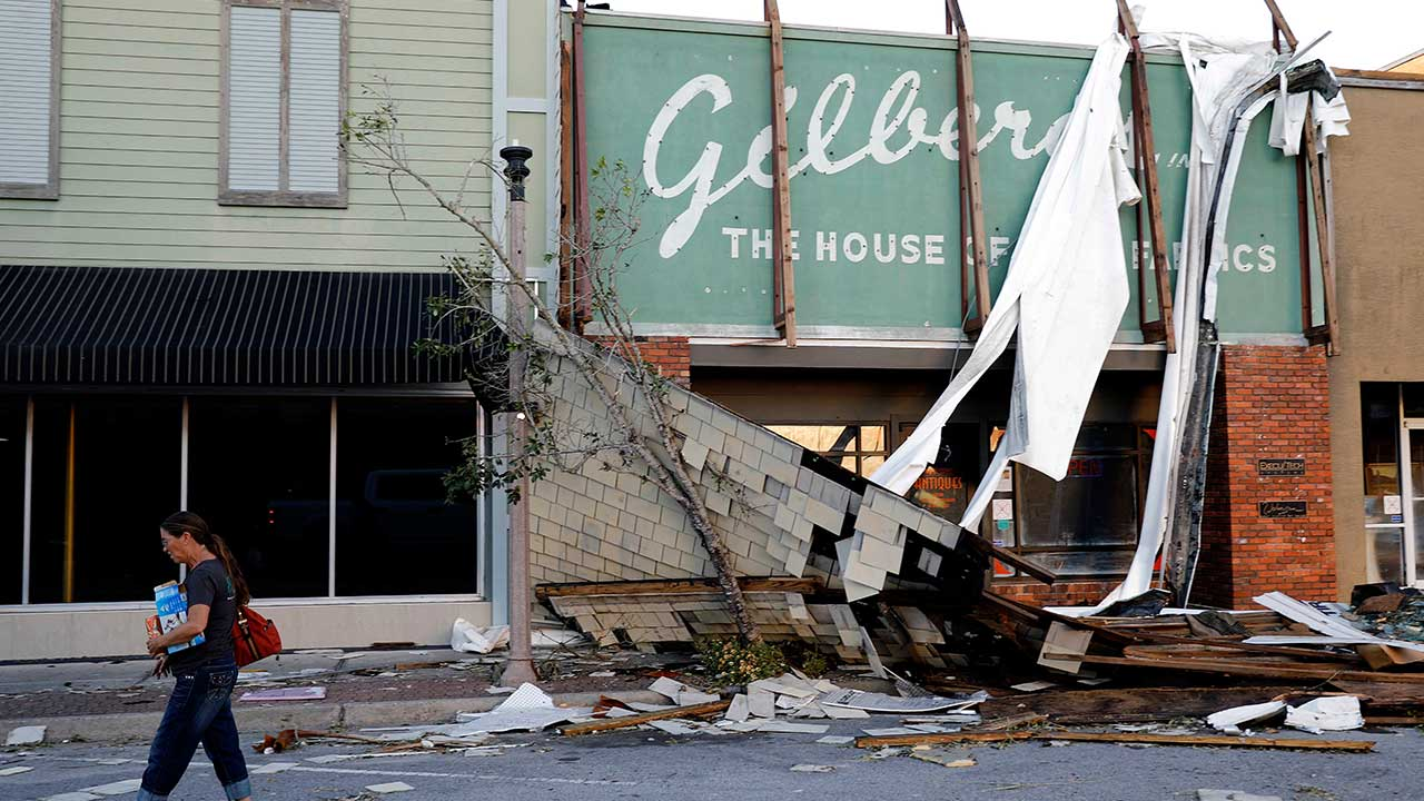 A woman walks past a damaged building in the historical downtown district in the aftermath of Hurricane Michael in Panama City, Fla., Friday, Oct. 12, 2018.