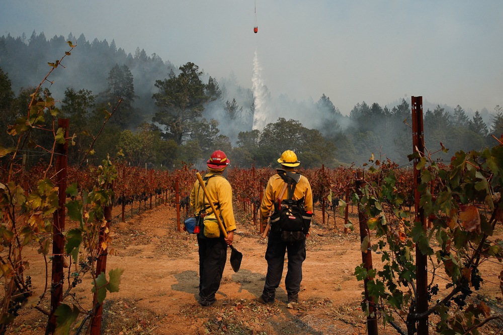 Firefighters Mike Beeman, left, and Chris Oliver watch as a helicopter drops water over a wildfire burning near a winery Saturday, Oct. 14, 2017, in Santa Rosa, Calif.
