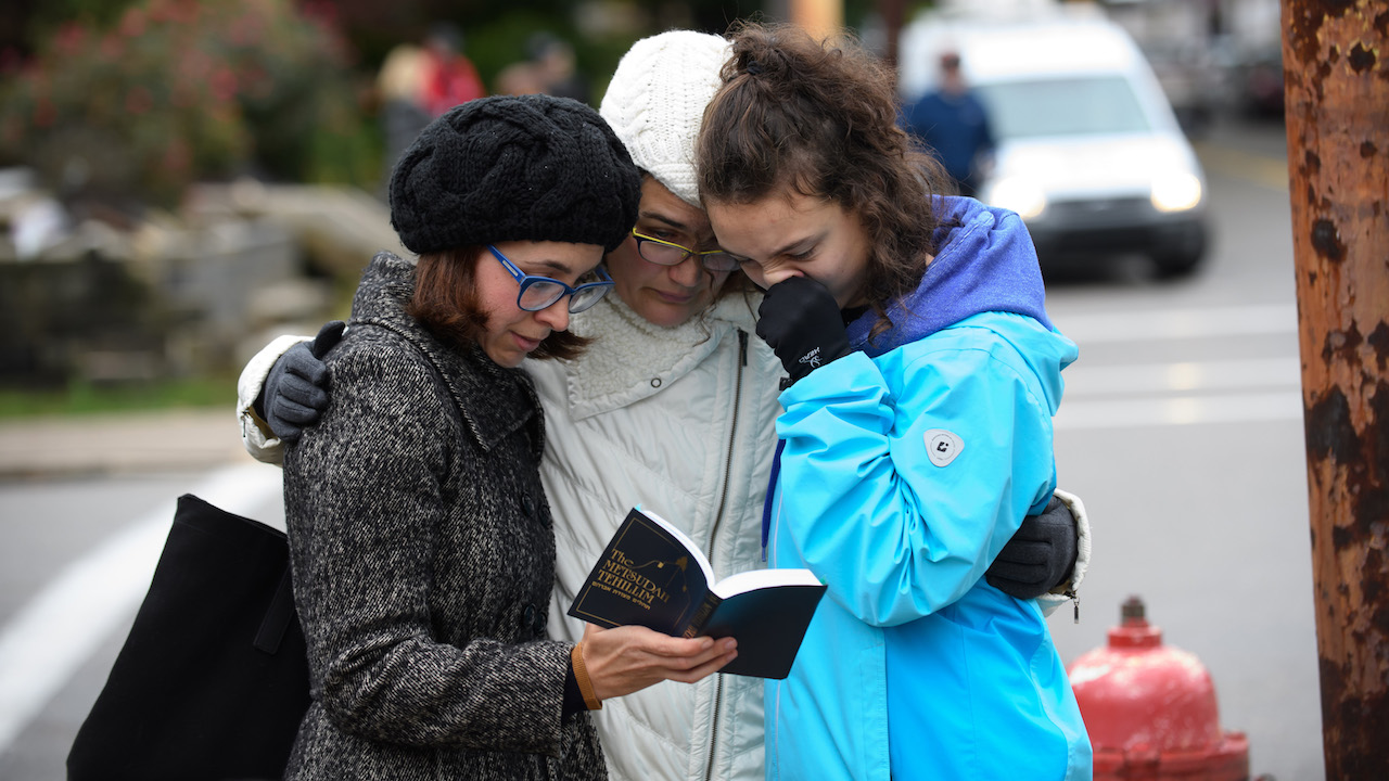 Tammy Hepps, Kate Rothstein and her daughter, Simone Rothstein, 16, pray from a prayerbook a block away from the site of a mass shooting at the Tree of Life Synagogue.