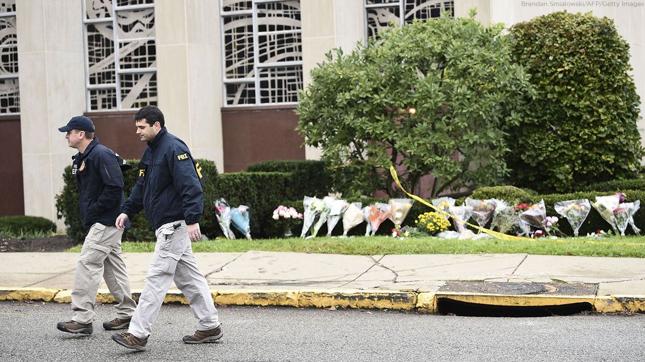 Members of the FBI walk past a memorial on October 28, 2018 outside of the Tree of Life Synagogue after a shooting there left 11 people dead in Pittsburgh on October 27, 2018.
