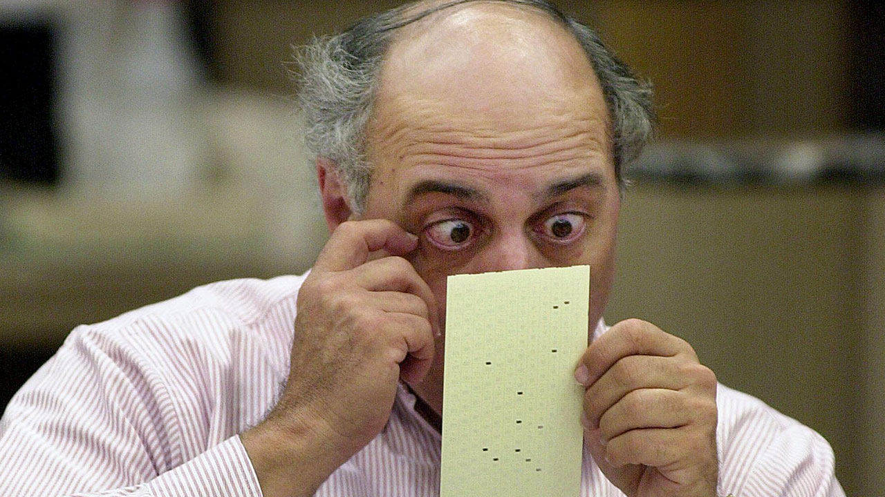 Broward County canvassing board member Judge Robert Rosenberg looks over a questionable ballot, 25 November 2000, at the Broward County Courthouse in Ft. Lauderdale, Florida.