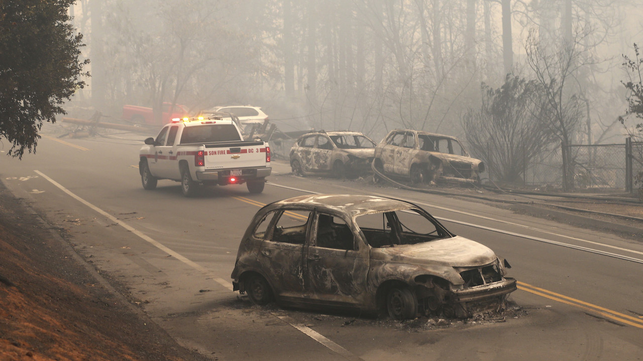 The burned-out hulks of cars abandoned by their drivers sit along a road Friday, Nov. 9, 2018, in Paradise, Calif.