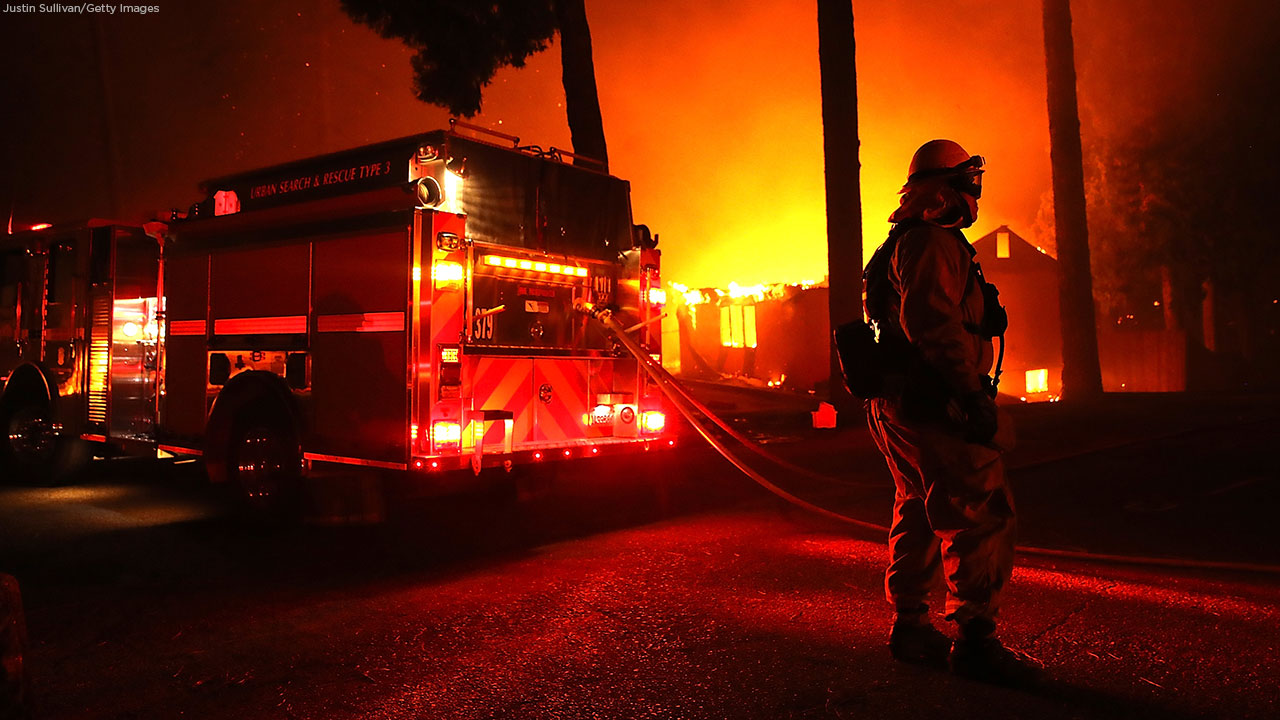 Firefighters try to save a building as the Camp Fire moves through the area on November 8, 2018, in Paradise, California.