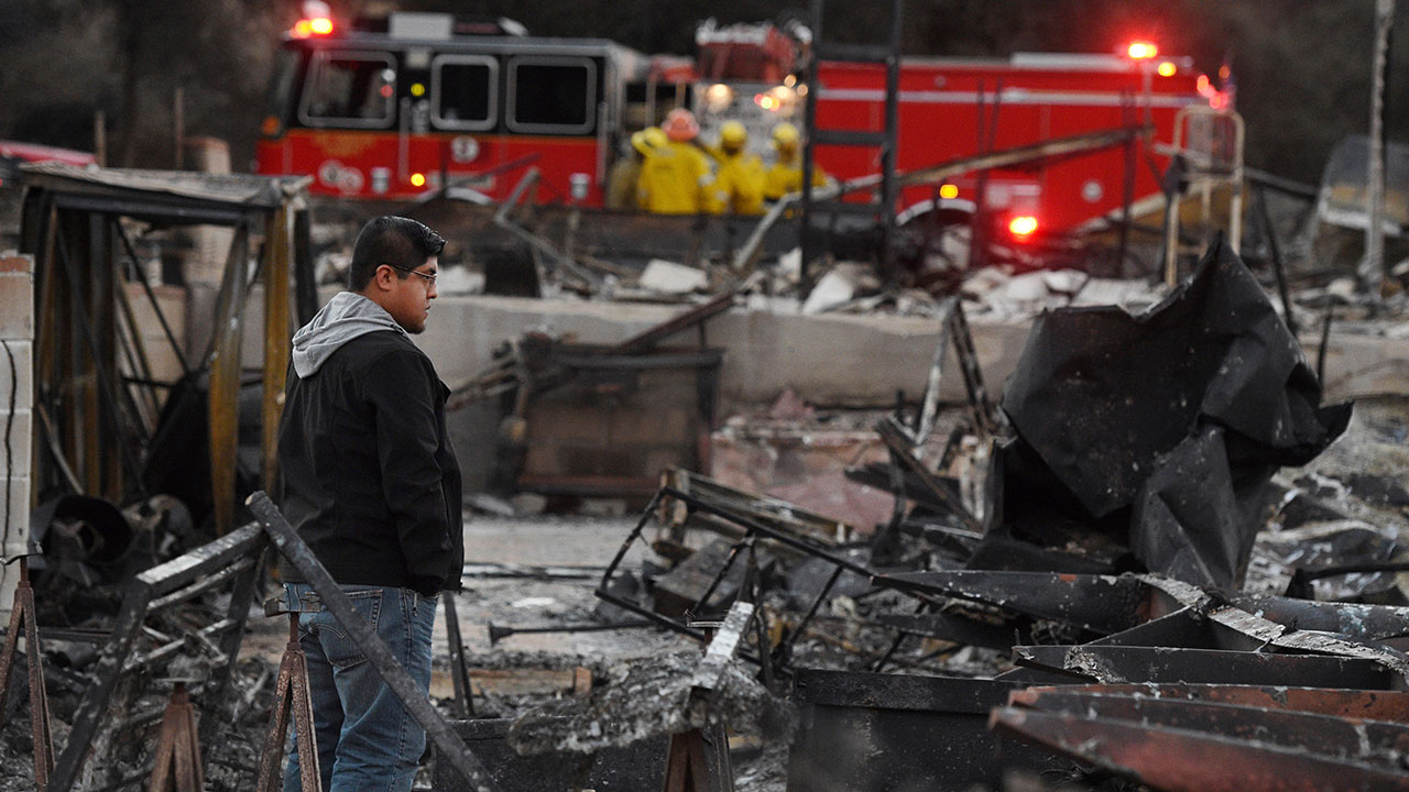 Ricky Alvarado looks over the charred remains of his home at the Seminole Springs Mobile Home Park, Sunday, Nov. 11, 2018.