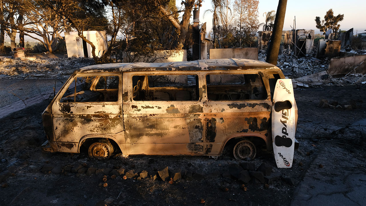 A burned surfboard and a van are all that remain in the front of a destroyed home in the Point Dome neighborhood in Malibu, Calif., Monday, Nov. 12, 2018.