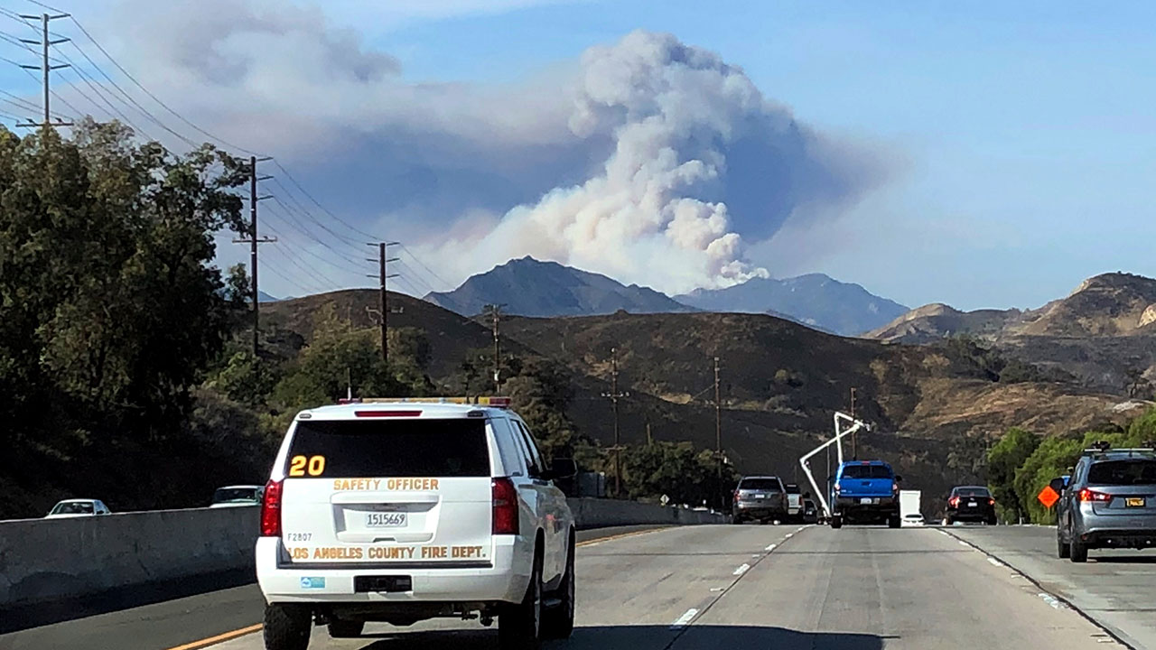 A large wildfire plume from a recent flareup near Lake Sherwood, Calif., is visible from Highway 101 north of Los Angeles, Tuesday, Nov. 13, 2018.