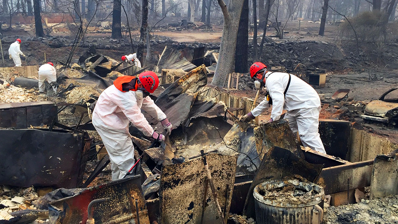 Volunteer rescue workers search for human remains in the rubble of burned homes in Paradise, Calif., Thursday, Nov. 15, 2018.