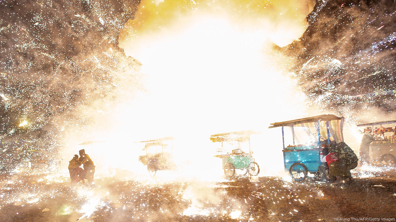 Revelers run away from a huge firework explosion from a hot air balloon during the Tazaungdaing Lighting Festival at Taunggyi in Myanmars northeastern Shan State.