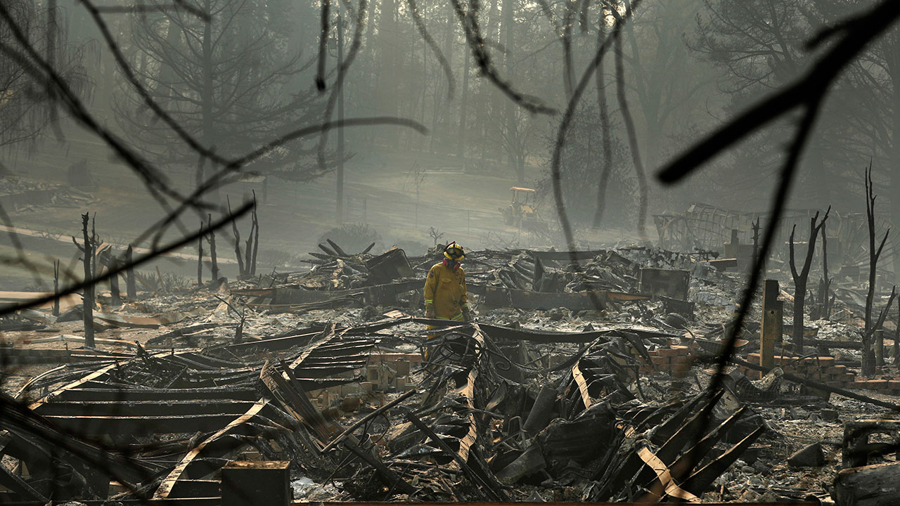 A firefighter searches for human remains in a trailer park destroyed in the Camp Fire, Friday, Nov. 16, 2018, in Paradise, Calif.