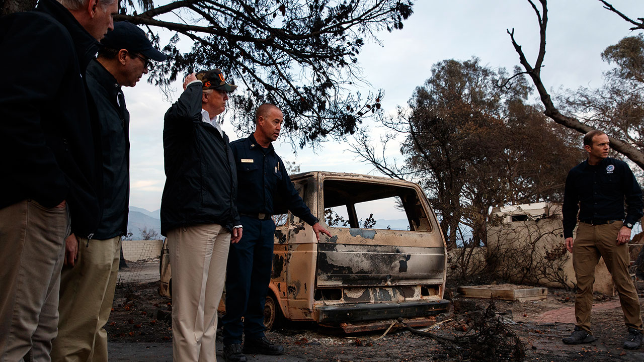 President Donald Trump stands near a burned out vehicle as he visits a neighborhood impacted by the Woolsey Fire, Saturday, Nov. 17, 2018, in Malibu, Calif.