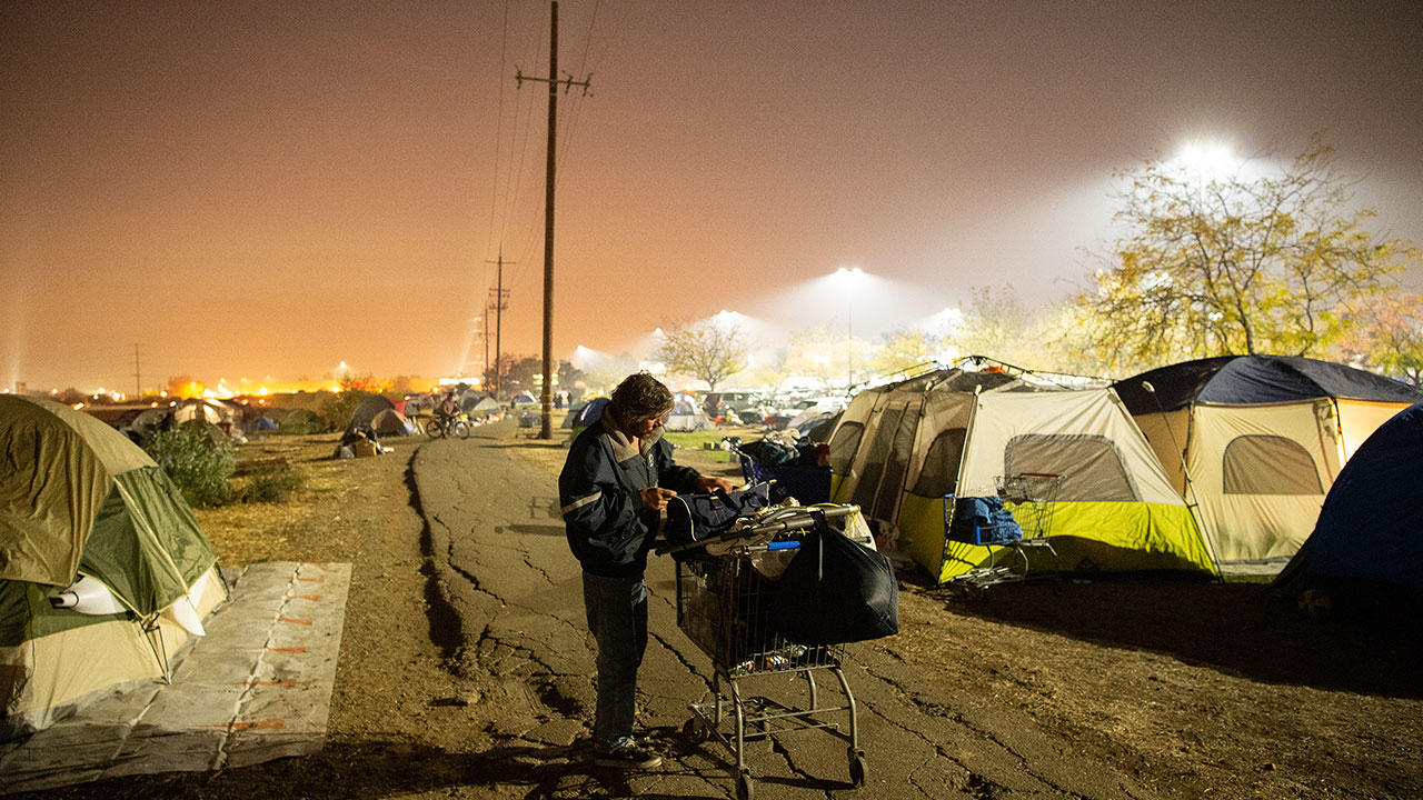 A man tends to his belongings at an evacuee encampment at a Walmart parking lot in Chico, California on November 19, 2018.