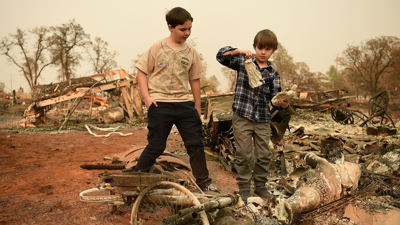 Jeremie (L) and and Jacob (R) Saylors look at religious statues they found in the burned remains of their home in Paradise, California on November 18, 2018.