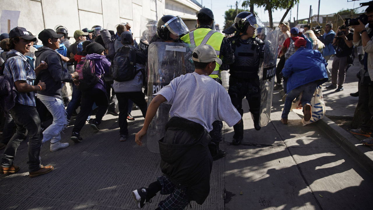 Migrants break past a line of police as they run toward the Chaparral border crossing in Tijuana, Mexico, Sunday, Nov. 25, 2018, near the San Ysidro entry point.