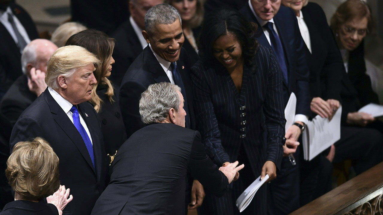 Former president George W. Bush greets former first Lady Michelle Obama at the funeral of his father George H.W. Bush.