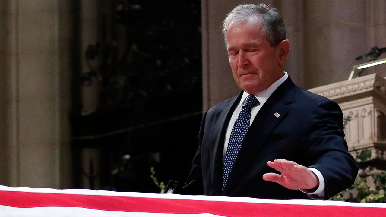 Former President George W. Bush touches the casket of his father, former President George H.W. Bush, at his state funeral.