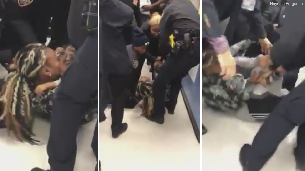 This image from video posted to social media shows a 1-year-old pulled from his mothers arms by police in New York on Friday, Dec. 7, 2018.