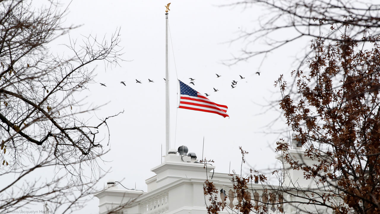 A flock of geese flies past an American flag at half-staff over the White House, Saturday, Dec. 1, 2018, in Washington.