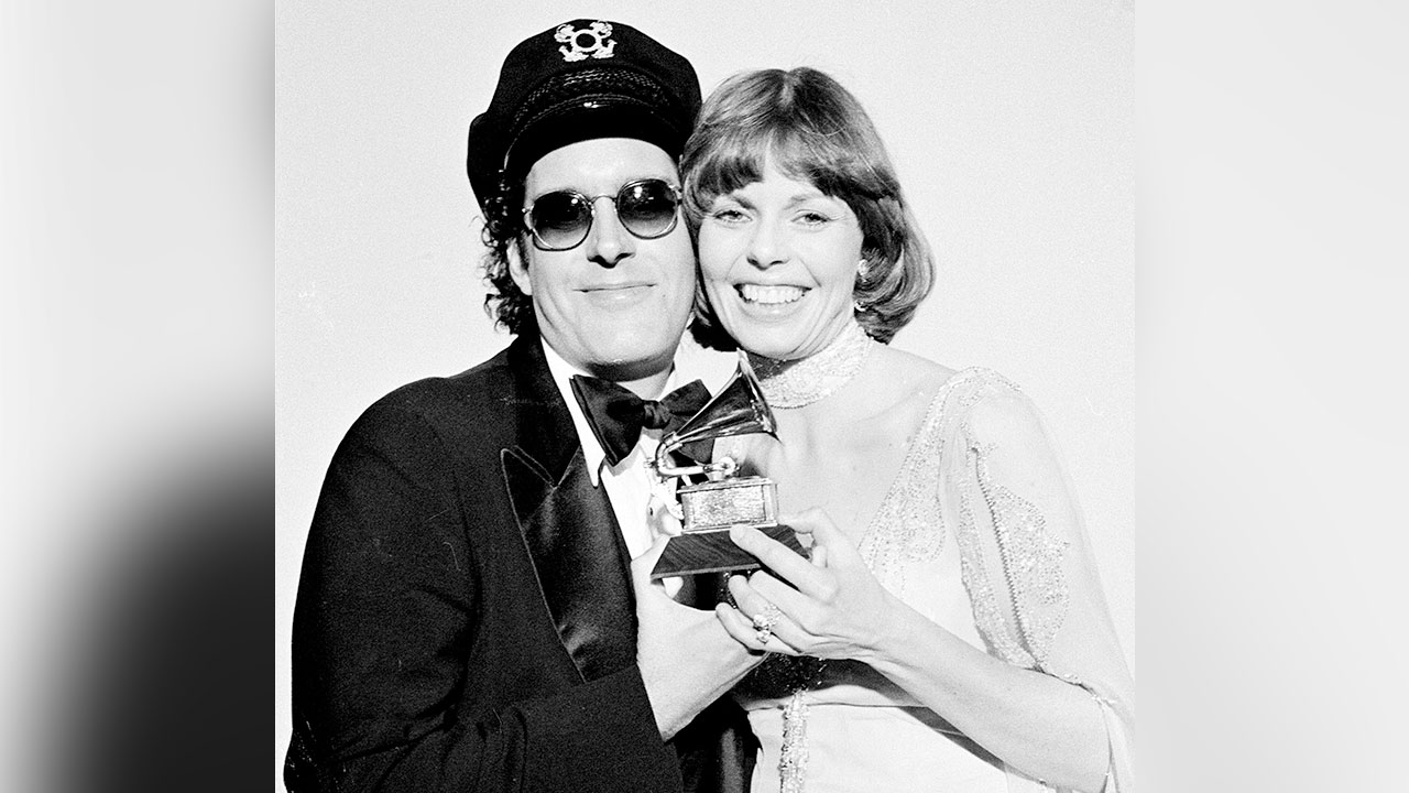 In this Feb. 28, 1976 photo, Daryl Dragon and his wife Toni Tennille, of Captain and Tennille, hold the Grammy award they won for record of the year for Love Will Keep Us Together.
