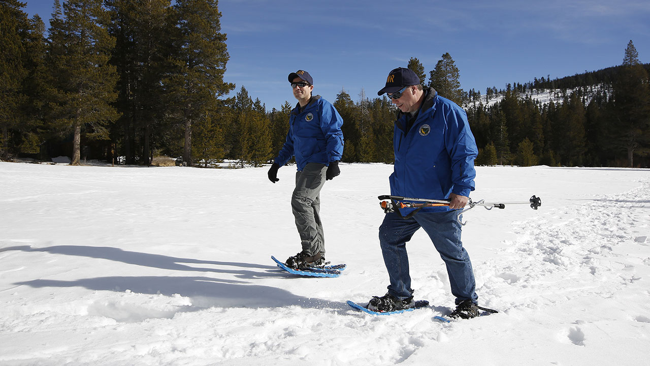 Department of Water Resources Water engineer John King and DWR State Climatologist Dr. Michael Anderson walk across a meadow after the first snow survey of the season, Jan. 3, 2019.