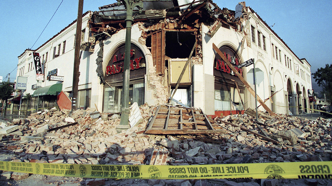 FILE - This Jan. 17, 1994 file photo shows bricks and debris surrounding a building housing Aras Pastry on Hollywood Boulevard in Hollywood following the Northridge earthquake.