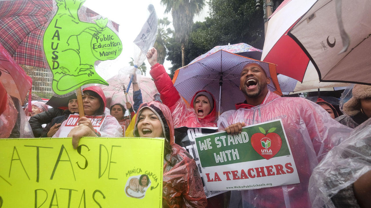 Teachers and supporters hold signs and umbrellas in the rain during a rally.