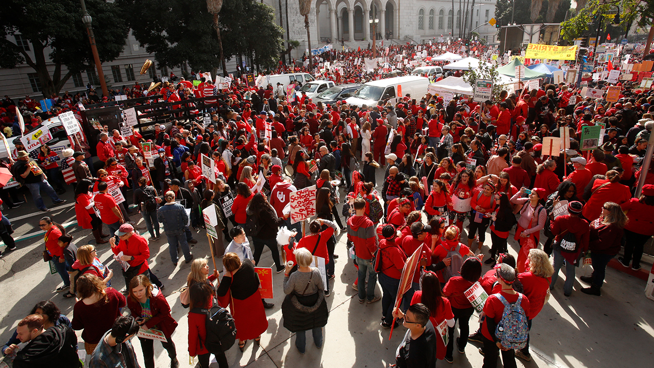 Los Angeles Police officers guard the entrance to City Hall as teachers, parents and students picket outside City Hall in Los Angeles, Friday, Jan. 18, 2019.