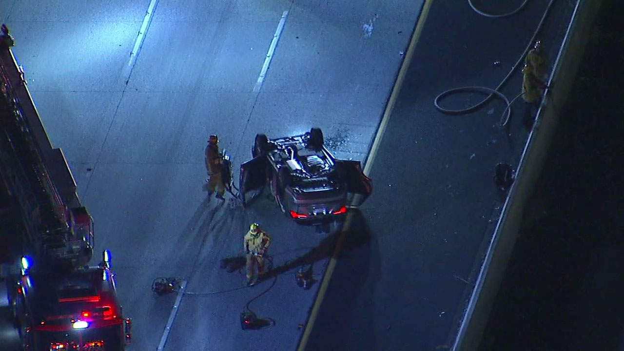 Authorities surveyed the scene after a vehicle overturned, leaving two people trapped inside and causing a backup on the westbound 118 Freeway in Pacoima.