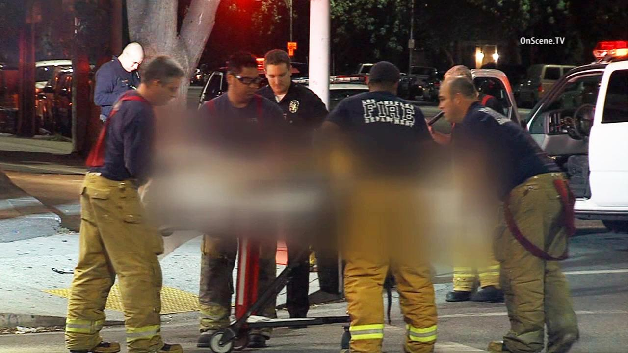 Emergency officials help a man who was stabbed in Van Nuys on Tuesday, Sept. 29, 2015.