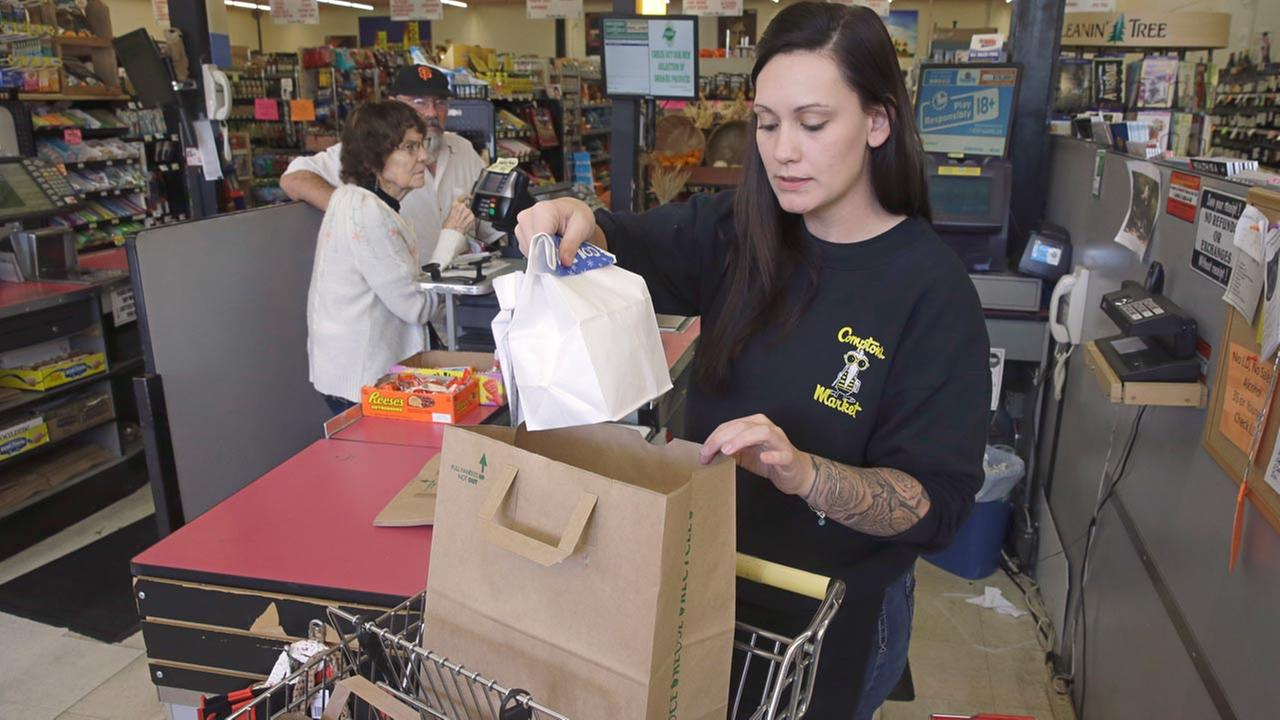 Checker Brittney Bounds bags groceries for customer Esther Franklin, left, at Comptons Market Tuesday, Oct 6, 2015 in Sacramento, Calif.
