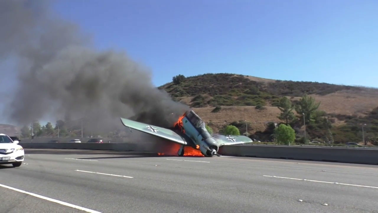A World War II-era small aircraft is shown on fire after the pilot crashed it into the westbound lanes of the 101 Freeway in Agoura Hills.