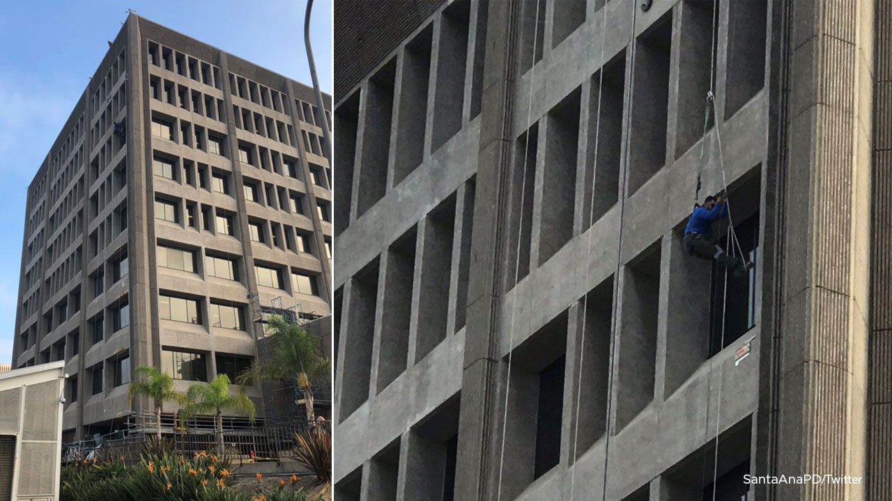 A man hangs from a federal building in Santa Ana on Tuesday, Oct. 23, 2018.