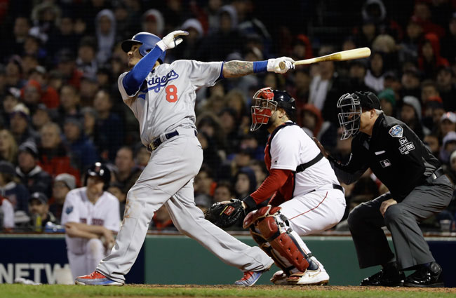 Los Angeles Dodgers Manny Machado hits an RBI sacrifice fly during Game 1 of the World Series baseball game against the Boston Red Sox Tuesday, Oct. 23, 2018.