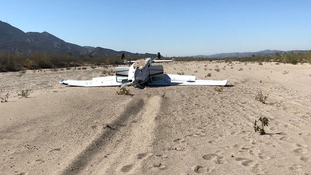 A small plane sits on its roof in a dry riverbed between Santa Paula and Fillmore after the pilot crash-landed it.