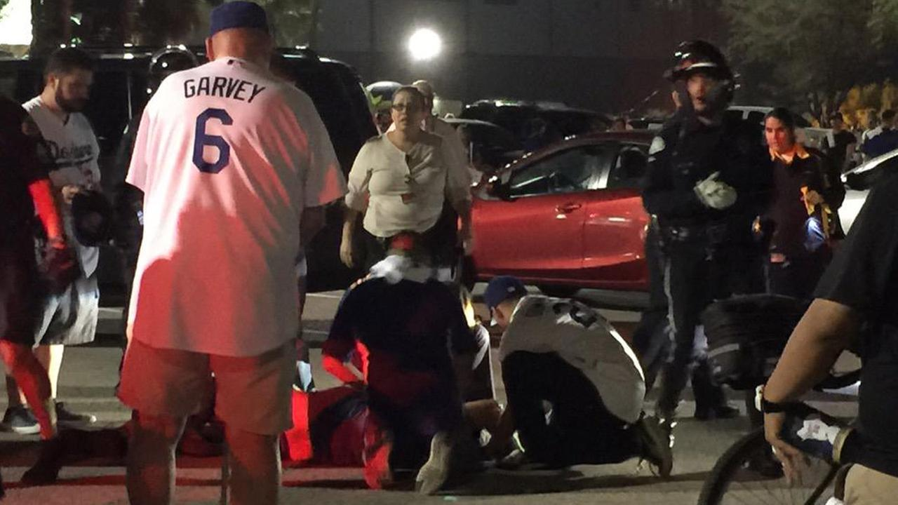 People attend to a fan who was critically injured in a fight that broke out during the NLDS opener at Dodger Stadium on Friday, Oct. 9, 2015.