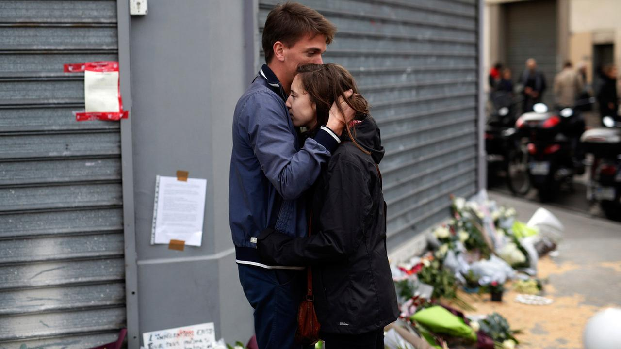 People react in front of the Carillon cafe and the Petit Cambodge restaurant in Paris Saturday Nov. 14, 2015, a day after over 120 people were killed in a series of terror attacks.