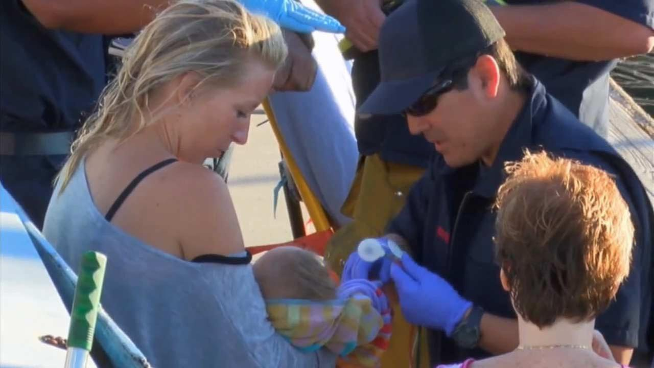A mother holds her child after successfully jumping off a burning boat in Venice Beach Saturday, Nov. 21, 2015.