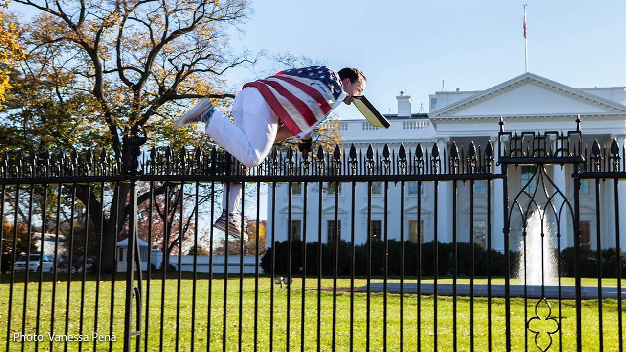 A man draped in an American flag jumps the White House fence on Thursday, Nov. 26, 2015.