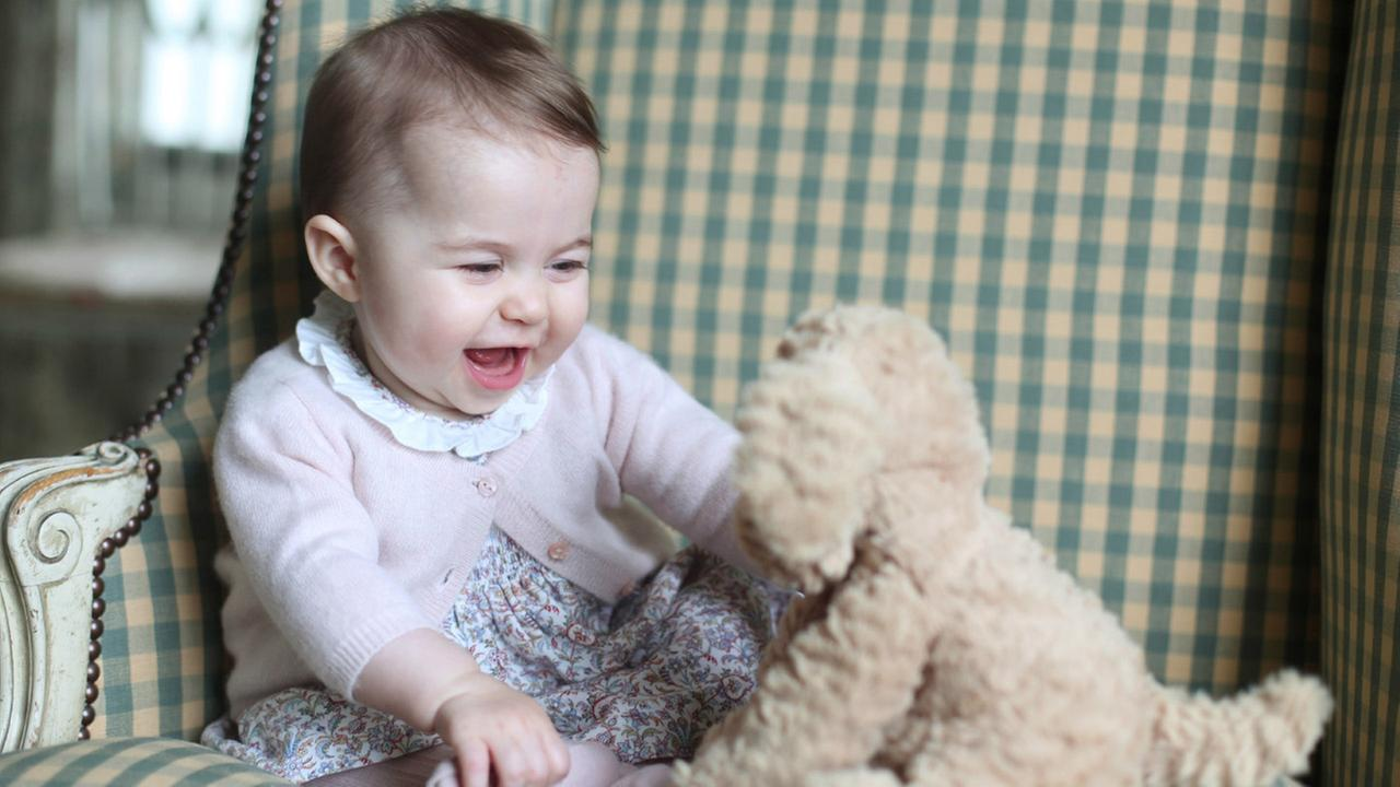 In this undated photo released Sunday Nov. 29, 2015, by Britains Duke and Duchess of Cambridge, showing Princess Charlotte with her cuddly toy dog, at Anmer Hall in England.