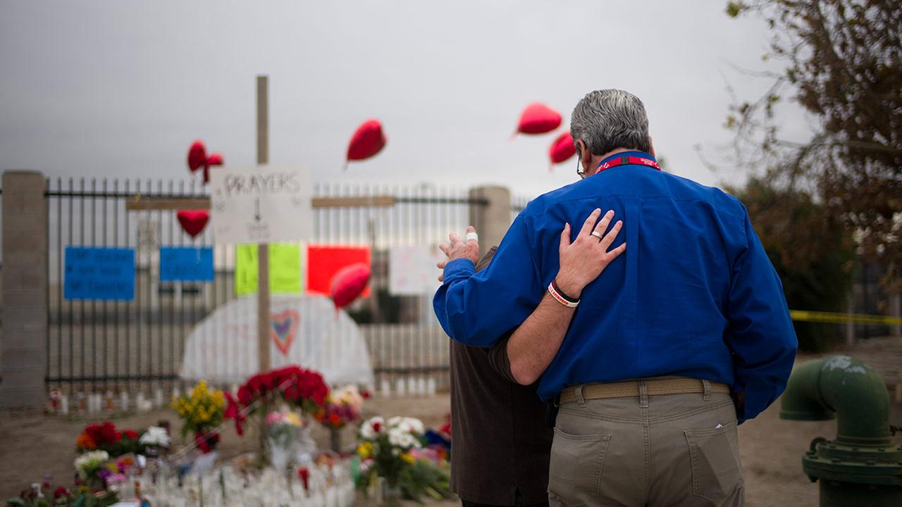 Chaplain Chuck Bender, right, prays with Michael Davila at a makeshift memorial honoring the victims of Wednesdays shooting rampage, Friday, Dec. 4, 2015, in San Bernardino.