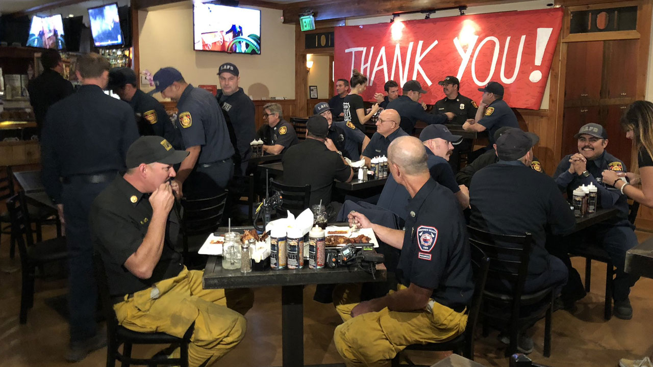 Firefighters enjoy a hot meal and sit near a large Thank You sign at Tavern 101 Grill and Tap House in Agoura Hills on Sunday, Nov. 11, 2018.