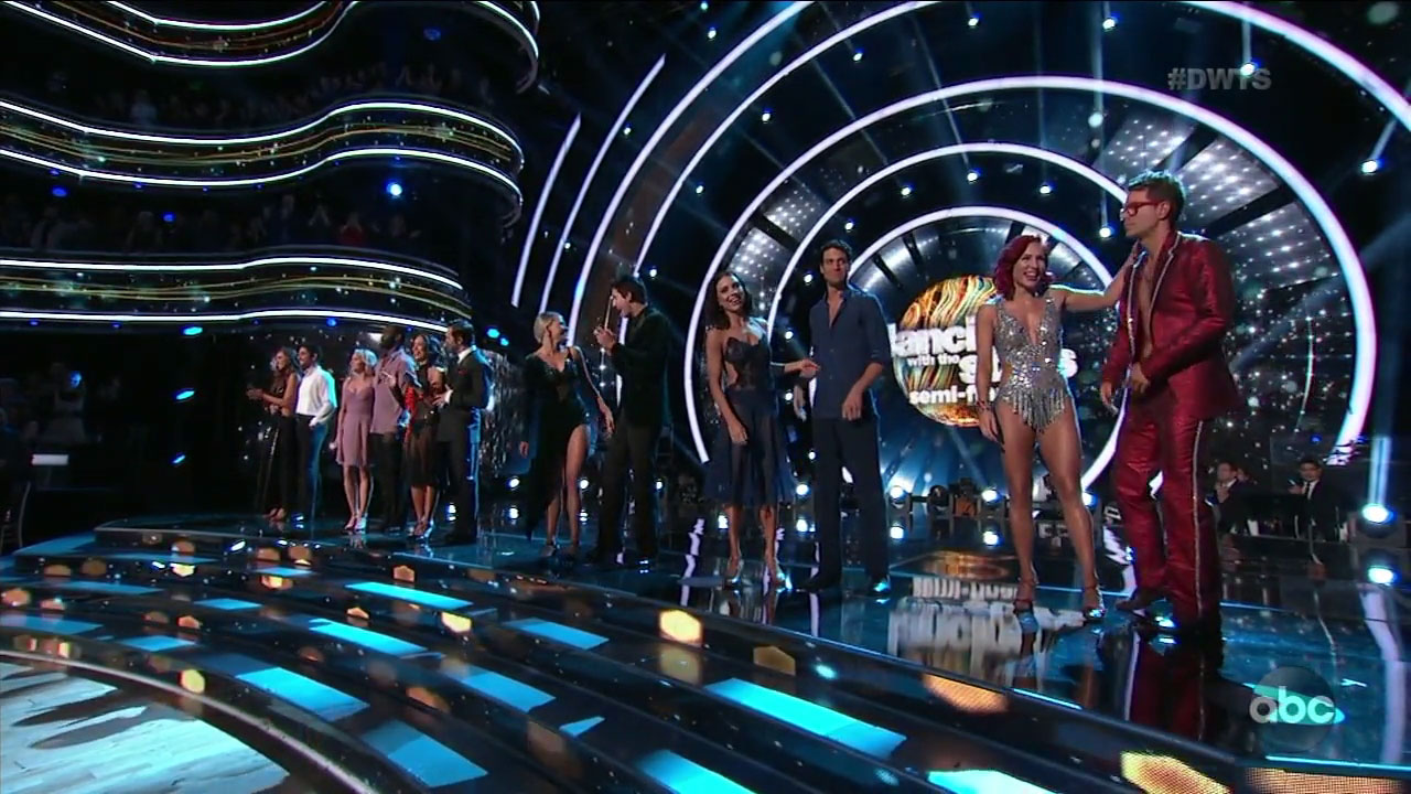 The remaining celebrities and their professional dancing partners stand on stage as they wait to perform.