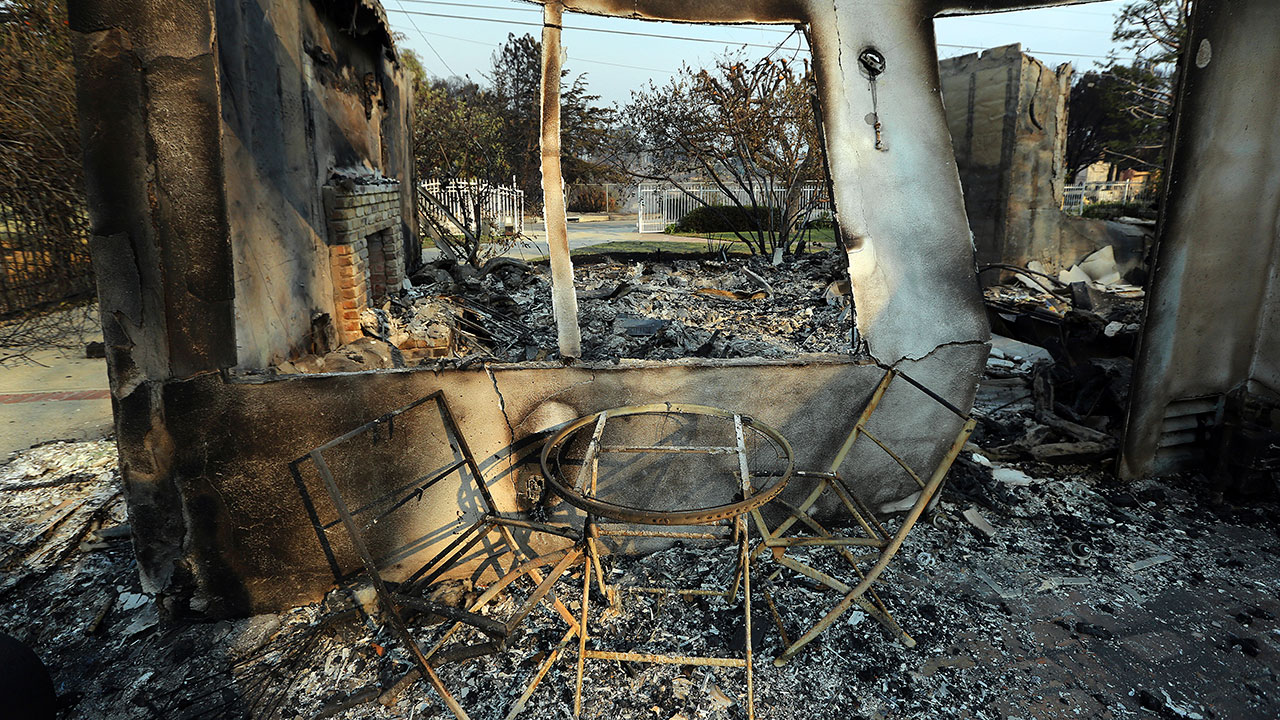 A table and chairs stand outside of one of at least 20 homes destroyed just on Windermere Drive in the Point Dume area of Malibu, Calif., Saturday, Nov. 10, 2018.