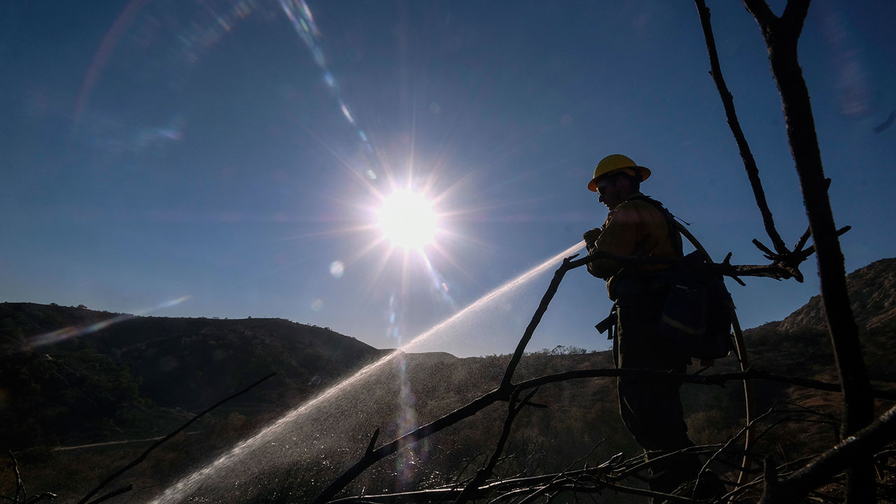 A firefighter sprays water on the remaining hot spots in an area in West Hills, Calif., Sunday, Nov. 11, 2018.