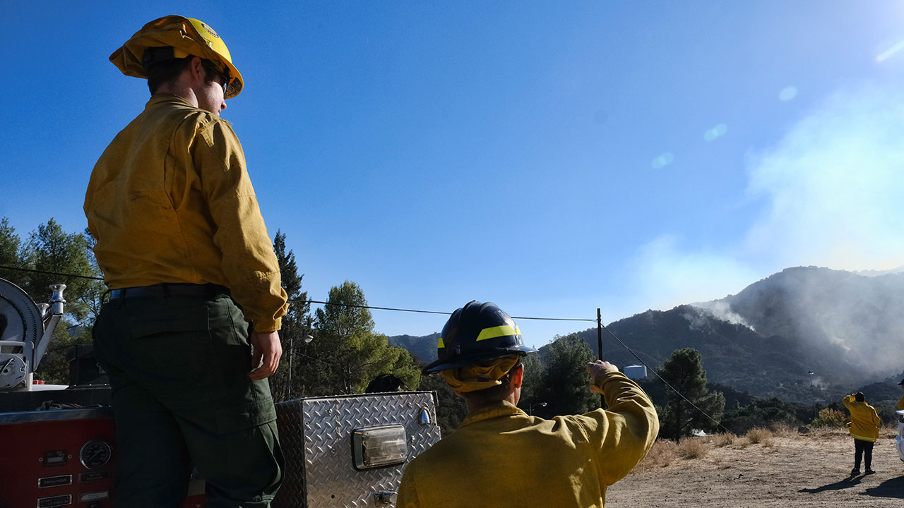 Firefighters with Mountains Recreation and Conservation Authority assess a wildfire on the side of a hill in Malibu Canyon in Malibu, Calif.
