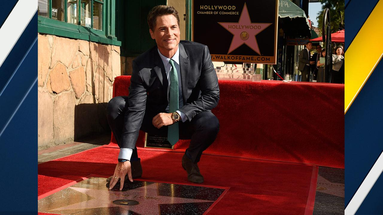 Actor Rob Lowe touches his new star on the Hollywood Walk of Fame on Tuesday, Dec. 8, 2015, in Los Angeles.