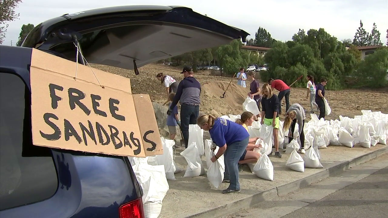 A sign for free sandbags is posted on a vehicle as people gather up the items to prepare for rains that could cause mudslides in the Woolsey Fire burn area.