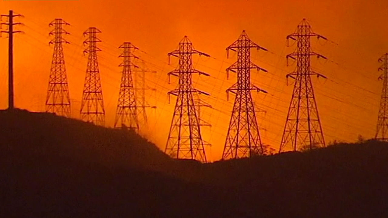 The Woolsey Fire burns a hillside near utility towers is shown in a photo.