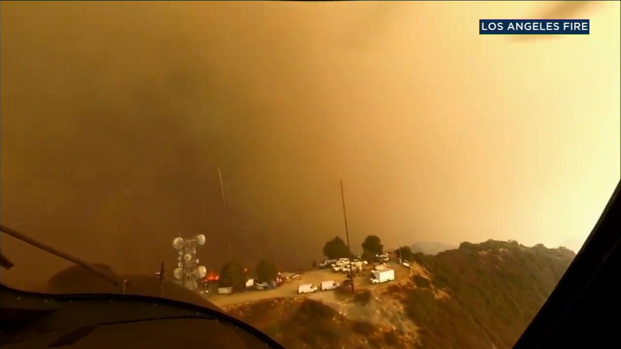 A daring, dramatic mountaintop rescue by a firefighter chopper crew in the middle of raging flames from the Woolsey Fire was caught on camera.